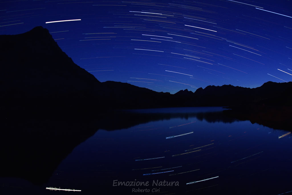 Star trail riflesso in un lago alpino